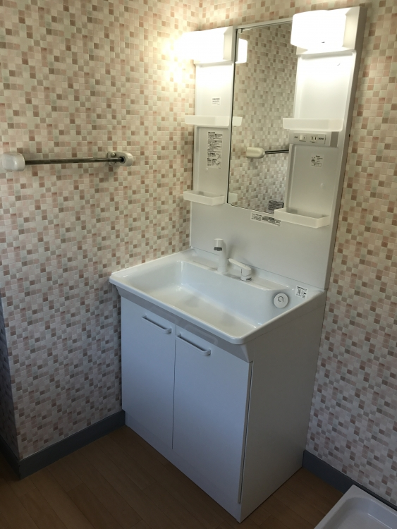 洗面所は洗面台を変え、クロスをピンクタイル柄にし、床は木目調クッションフロアでナチュラル系に。